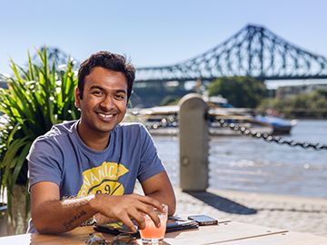 International Student hanging out by the Brisbane River in front of the Story Bridge
